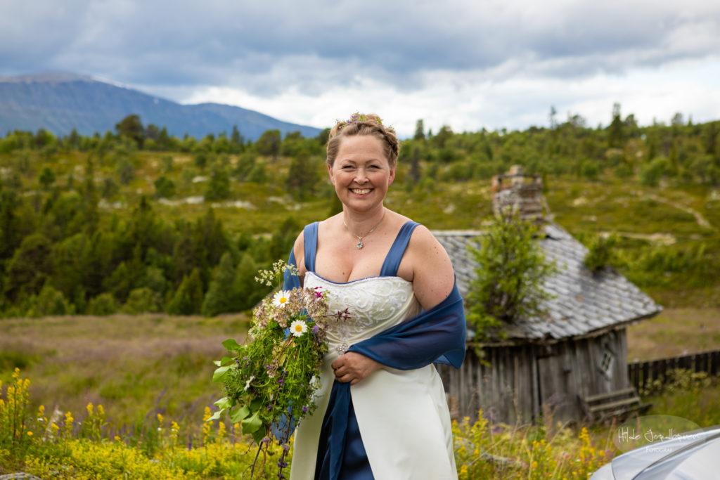 Marit kommer i brudekjole hun har sydd selv og bukett av markblomster.