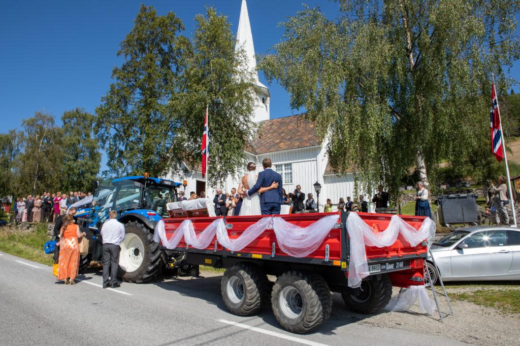 Utenfor kirken venter skyssen - traktor og tilhenger pyntet i brudestas