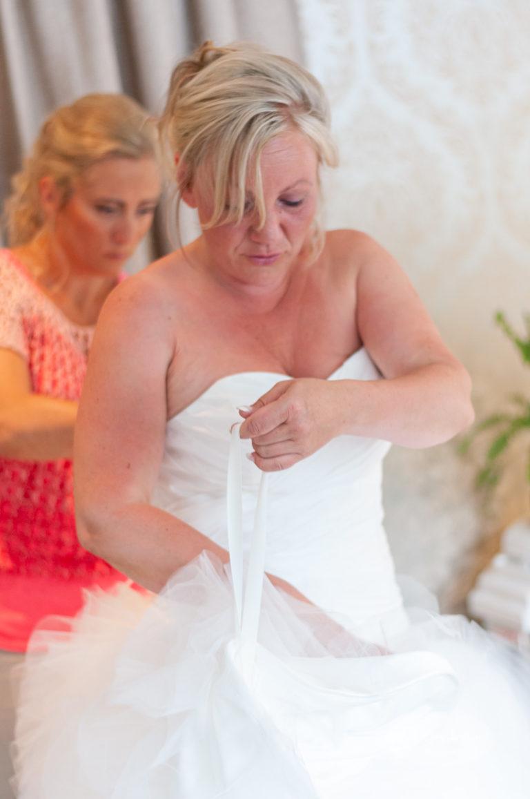 Bruden får hjelp fra sin forlover til å ordne kjolen