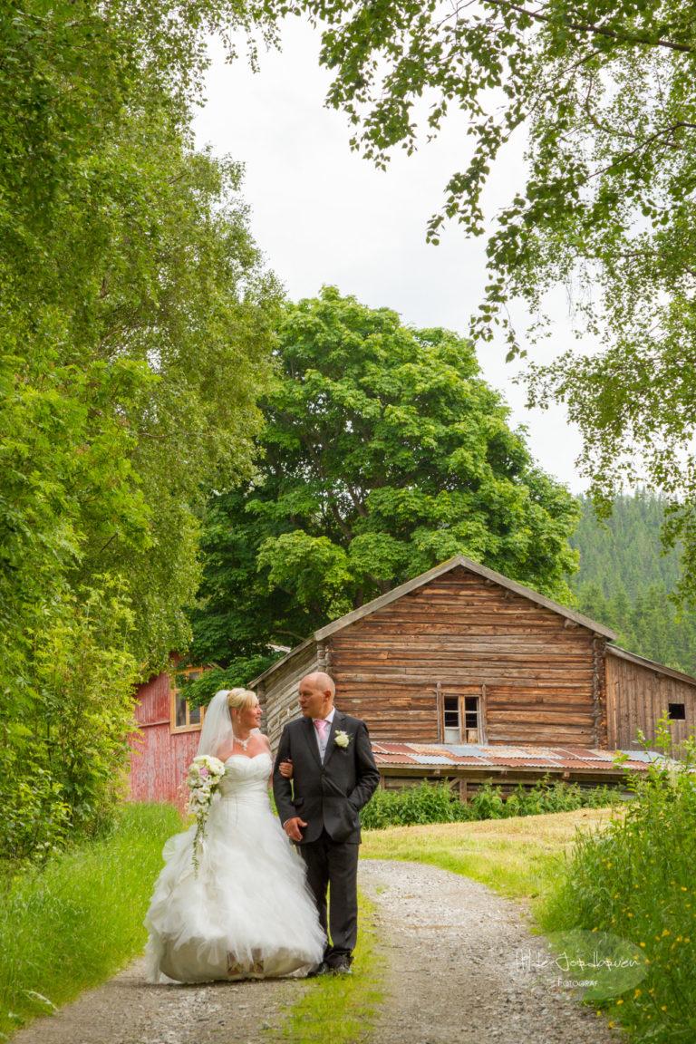 Brudepar på vegen med gård i bakgrunnen