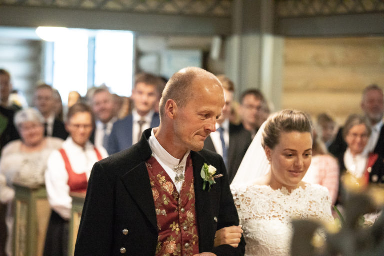 Bruden følges opp kirkegulvet av sin far